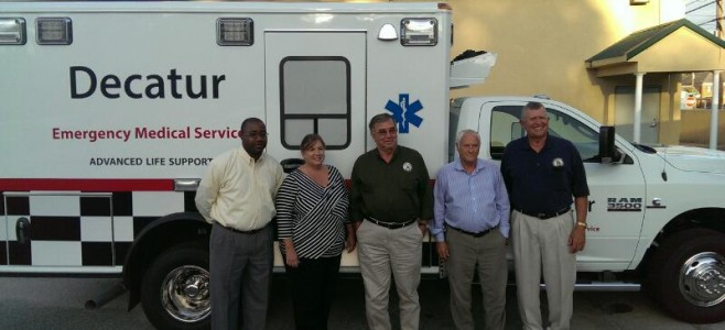 Decatur County commissioners stand in front of one of the new ambulances