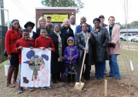 With the tree in the ground to the right, Janet Mitchell's family and colleagues gathers around her. From the left, front, are Keenan Phillips and Braylon Phillips, who are the Arbor Day flag, and Jaisha Harris; middle row, Shemelia Bush, Linda Hitchcock, Amy Robinson, Roxie Marshall, Bonnie Provence, Janet Mitchell (holding the shovel) and Ethel Willis; back row, Bud Holleman of Southern Forestry, Decatur County Commissioner George Anderson, Jones-Wheat Elementary School Principal Larry Clark, Decatur County Administrator Gary Breedlove and Suzanne Brandt of Keep America Beautiful.