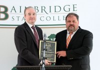 District Attorney Joe Mulholland (left) presents Bainbridge State College Police Chief James E. Spooner, Jr., with the 2015 Justice Award for his commitment to serving justice.