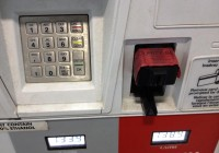 """One example of a skimmer at a gas pump. The red tape says """"Security Seal"""", but it's just a trick to cover the fact that the plastic piece that accepts a credit card has been tampered with."""