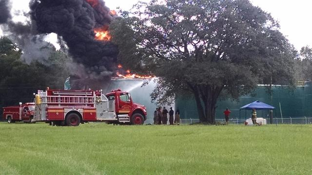 Firefighters and other emergency personnel working at the scene of the explosion and fire. You can see water being sprayed on the holding tank.