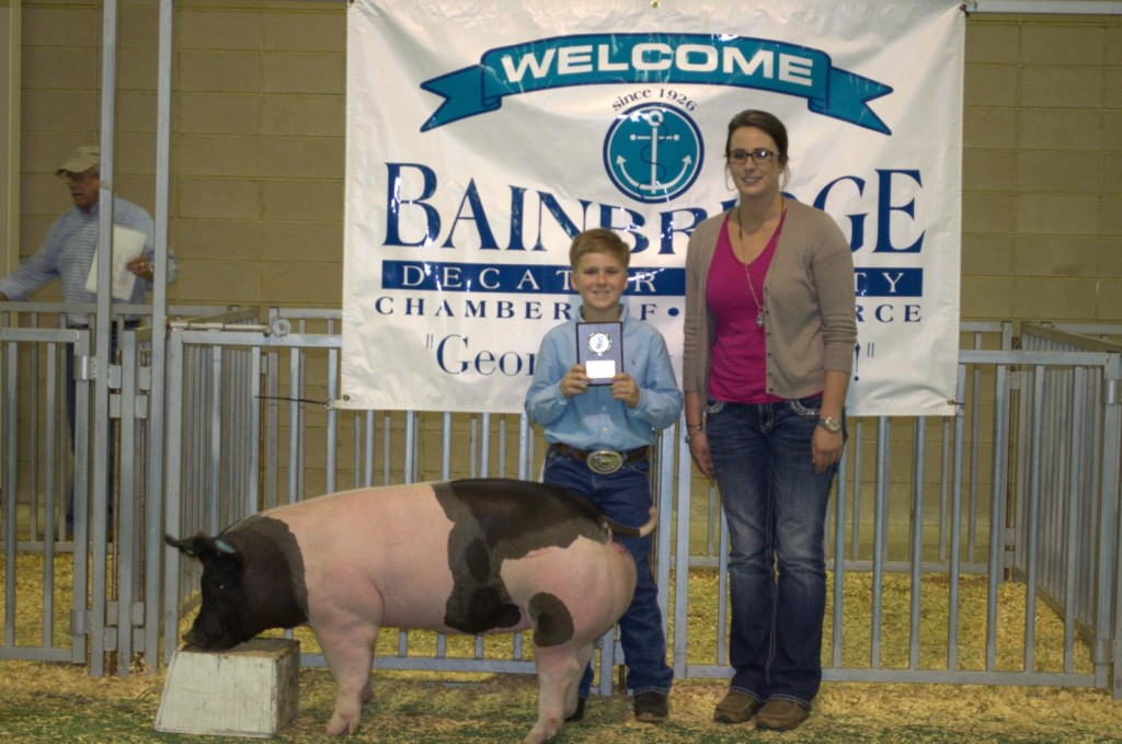 Carson Lynn and his Grand Champion Market Hog with show judge, Victoria Hill